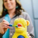 A dental hygenist demonstrates proper brushing.