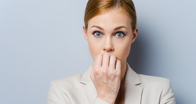 blonde woman wearing a beige suit jacket covering up her mouth looking afraid