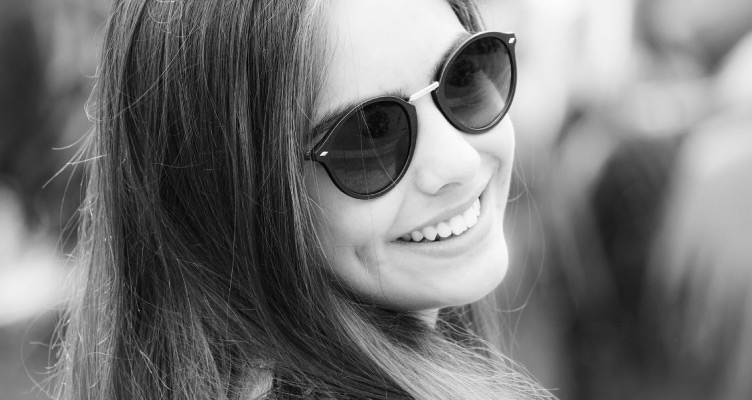 black and white photo of young girl wearing sunglasses and smiling