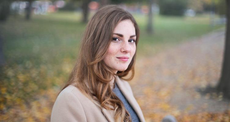 brunette woman sitting in a park, wearing beige blazer