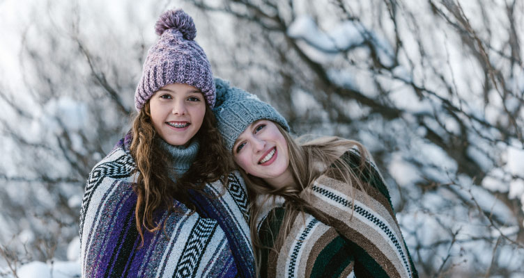 Two smiling teenage sisters, one with braces, wear beanies and wrap themselves in striped woven blankets