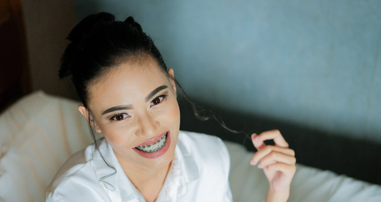 girl smiling with braces twirling a hair strand