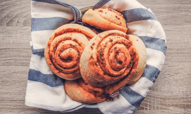 Aerial view of 5 spiral dinner rolls in a basket with a striped blue and white cloth