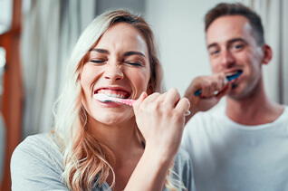 couple brushing their new dental implants