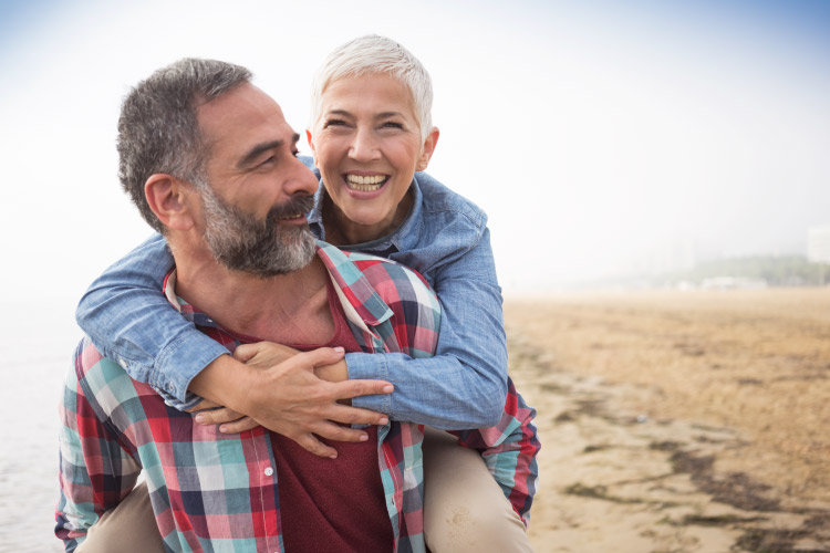 A salt-and-pepper-haired husband gives a piggy-back ride to his white-haired smiling wife on the beach