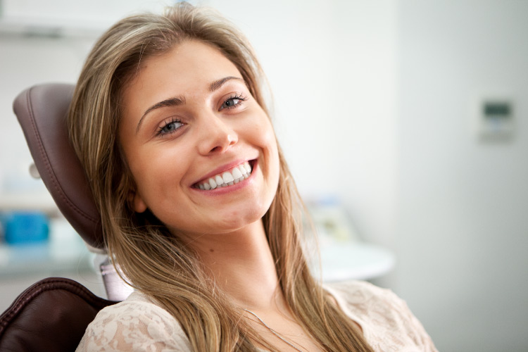 Brunette woman with a dental implant smiles while sitting in a dental chair in Fayetteville