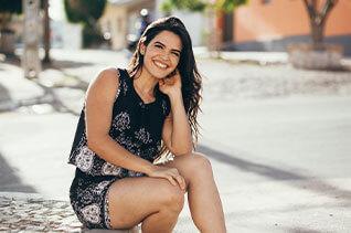 Woman sitting down on sidewalk