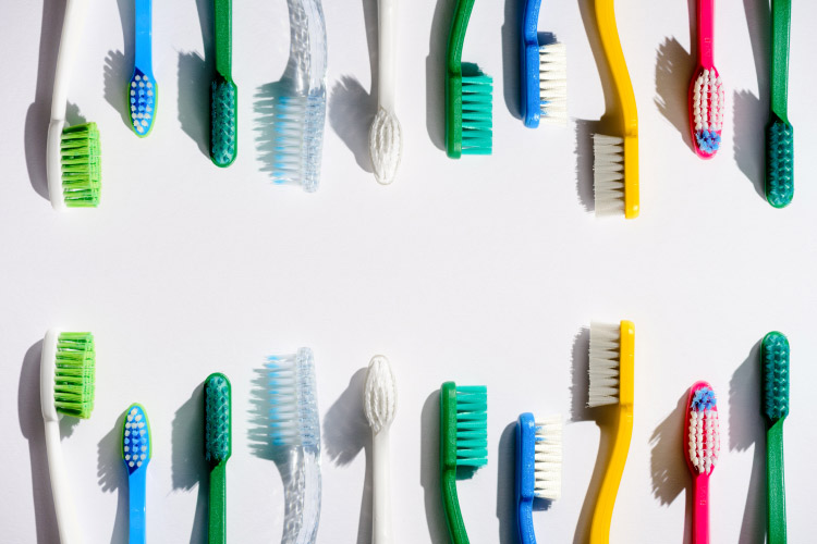 Aerial view of a variety of colored manual toothbrushes, each one a new toothbrush, against a white background