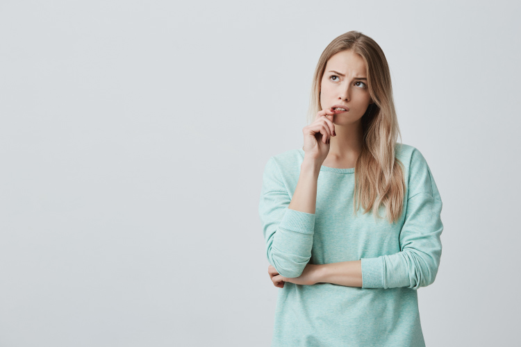Blonde woman in a mint sweater bites her lip and wonders how her overall health affects her gums