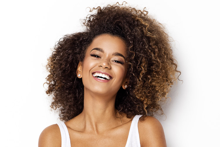 Curly-haired woman smiles with dental implants in Fayetteville, AR
